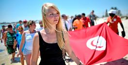 Tourists carry a Tunisian flag along Marhaba beach yesterday in a tribute to the victims of the massacre. Photo: Getty