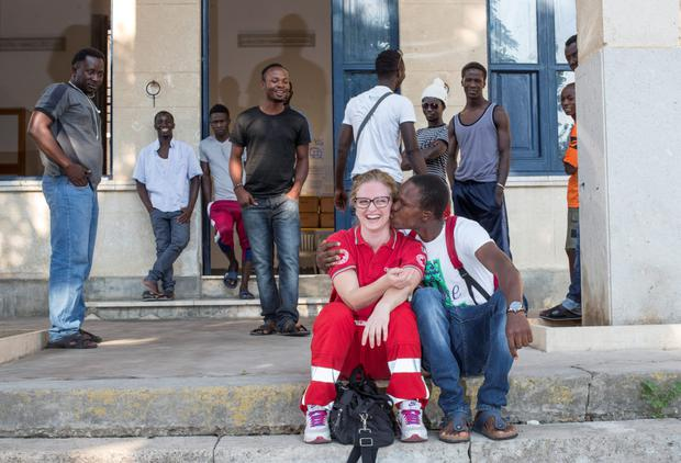 Red cross staff member Annamaria Ginestra gets a kiss from a migrant at the red cross centre in Alcam, Sicily. Photo: Mark Condren