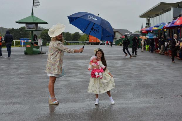 Harrett Murphy Carroll and her daughter Claudia, from Cork, arrive at Killarney Racecourse in the rain