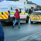 A protester throws a brick at a garda car during the incident in which Joan Burton was trapped for two hours