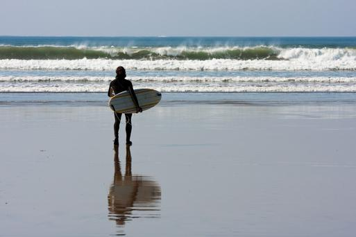 Man with surfboard...Man with surfboard watching Waves in Clare
