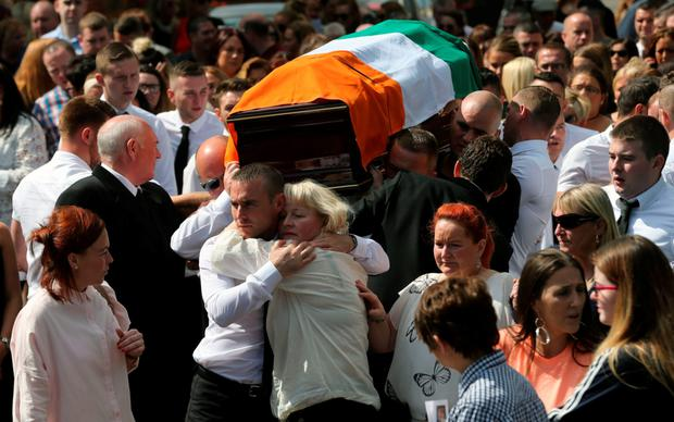 Kevin McGuigan's widow, Dolores, is comforted as the coffin of the former IRA man is carried from St Matthew's Church in east Belfast following his funeral this week Photo: PA