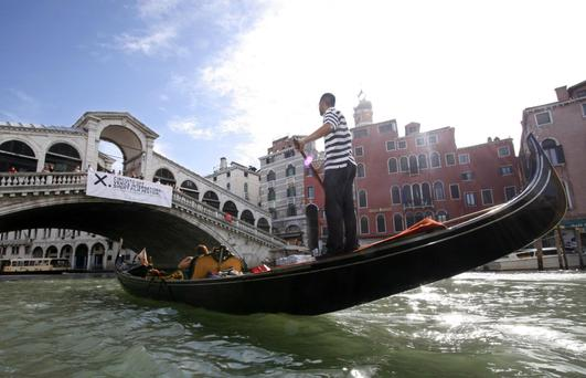 TROUBLED WATERS: A gondolier rows his gondola next to Rialto Bridge in Venice. The mayor of Venice has said he never wants to see gay pride march in his city. They are the 'height of kitsch', he said