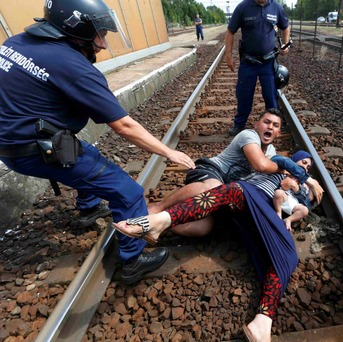 Hungarian policemen stand by a family of migrants who tried to flee the railway station in the town of Bicske