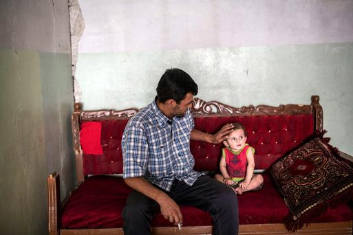 Aylan Kurdi's father Abdullah Kurdi sits with his nephew in a relative's house in Kobane, where the grieving man returned to bury his family at the weekend