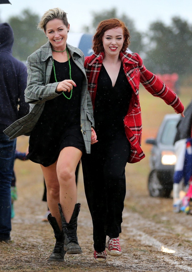Niamh Philips and her daughter Ceili from Omeath, Co Louth, dash for shelter from the rain at the annual Vintage Day in Knockbridge, Co Louth Photo: David Conachy