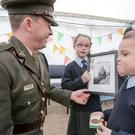 14/09/2015 Lt. Seamus Shannon speaking to Conor McDonagh aged 4 and his sister Kyla aged 7 at a ceremony in St. Patrick's National School, Cornanool, Castlebar, Co. Mayo where he presented them with a national flag and a copy of the 1916 proclamation. Kyla is holding a photograph of her Great Grandfather, Edward Ludden who served in The Irish Army between 1939 and 1946. Photo : Keith Heneghan / Phocus