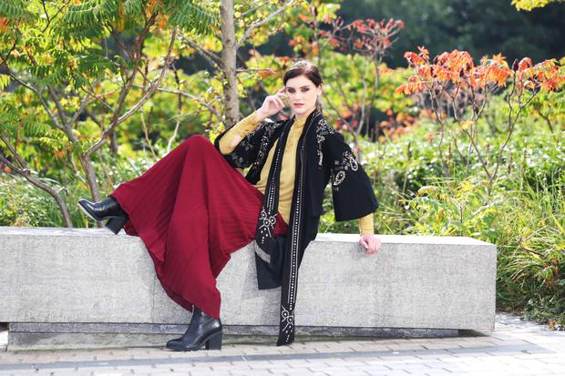 Abbey Harris wears an embellished coat (€163), mustard blouse (€103) and pleated skirt (€220), all from Biba at House of Fraser, with Clarks shoes (€90).