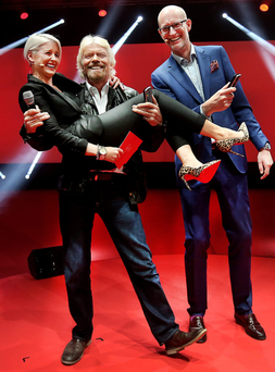 Richard Branson lifts presenter Sinéad Kennedy alongside Magnus Ternsjo, chief executive of Virgin Media, at the RDS Photo: Steve Humphreys