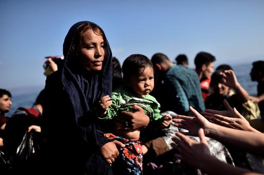 A migrant woman holds a child as refugees and migrants arrive at the Greek island of Lesbos after crossing the Aegean sea from Turkey on October 5, 2015