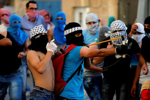 A Palestinian protester uses a slingshot to hurl a stone towards Israeli police during clashes in Shuafat, an Arab suburb of Jerusalem