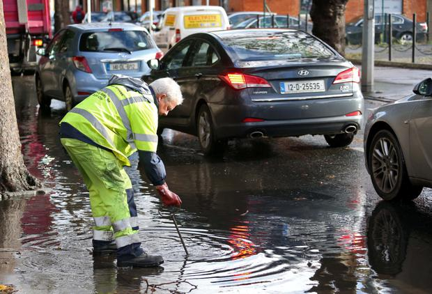 A Dublin City Council worker relieves flood waters on the North Circular Road in the capital