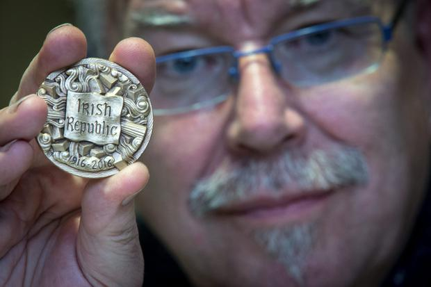 Artist Robert Ballagh shows one of the 1916 commemorative medals at Glasnevin Cemetery, Dublin