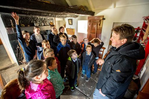 Tour guide Paul Gibson with pupils from Kiltyclogher National School at the birthplace of Seán Mac Diarmada in Kiltyclogher, Co Leitrim