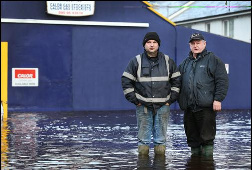 Anthony and Peter Madden from Peter Madden Fuels stand in flood water outside their premises in Ballinasloe yesterday