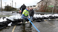 Council workers try to hold back the River Shannon from bursting its banks along Deerpark Road in Athlone town
