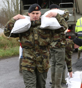 Soldiers from the 12th Battalion, Sarsfield Barracks, Limerick, help deliver sandbags in Clonlara, Co Clare