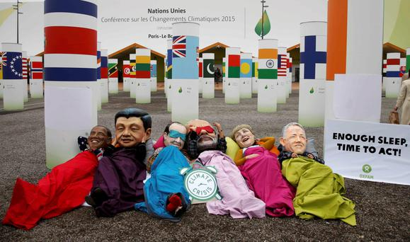 Activists of global anti-poverty charity Oxfam wearing masks depicting some of the world leaders – US President Barack Obama, Chinese President Xi Jinping, French President François Hollande, India's Prime Minister Narendra Modi, German Chancellor Angela Merkel and Australia's Prime Minister Malcolm Turnbull – during a protest in Paris