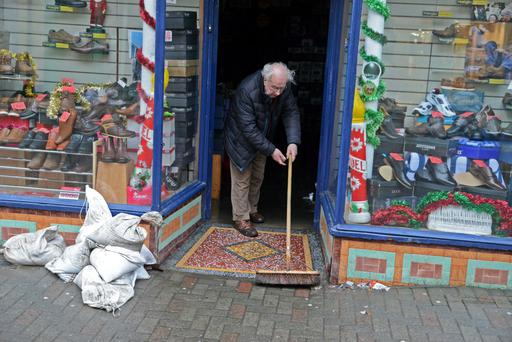 Michael Crowley cleaning up after his shoe shop was flooded in Bandon, Co Cork