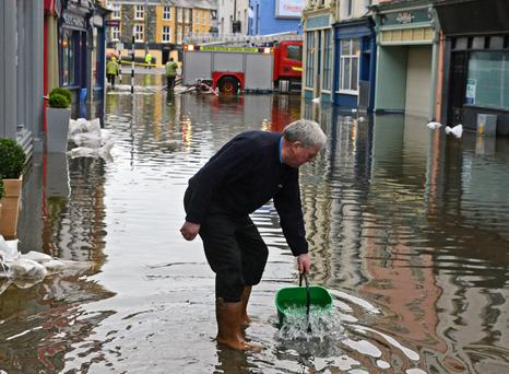 Jim Deane cleaning up after water entered Shortens Boutique, on South Main Street, in Bandon, Co Cork
