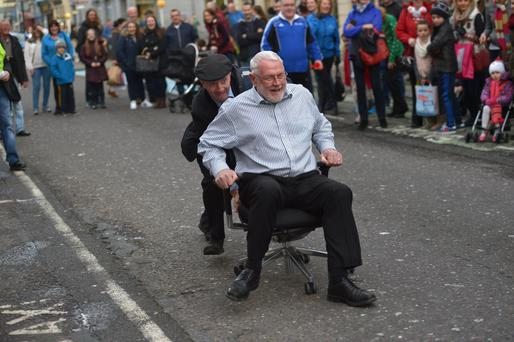 Michael Healy Rae pushes Martin Ferris in the Christmas office chair race in Tralee. Photo: Domnick Walsh
