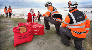 Members of the Irish Coast Guard rescue Santa after he fell out of his sleigh onto Dollymount Strand. Photo: Steve Humphreys