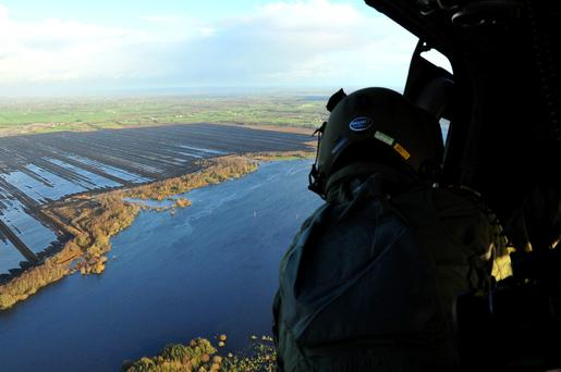 A Defence Forces plane flies over flooded bogs beside the River Suck in Ballinasloe earlier this month