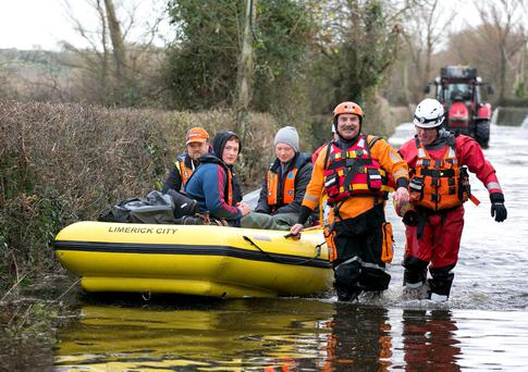 Mike Hogan (left) with his sons Mark and Seán, from Clonlara, Co Clare, being rescued from their home by members of the Civil Defence earlier this month. Photo: Arthur Ellis