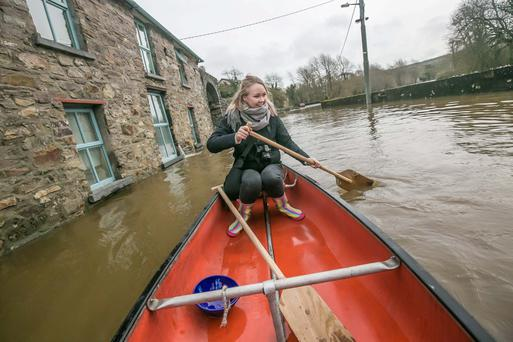 Amelia Caulfield rows along the street in Thomastown, Co Kilkenny, after her home was flooded when the swollen River Nore burst its banks. Photo: Pat Moore