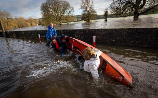 Tánaiste Joan Burton and junior minister Ann Phelan take a tumble into the Nore during their visit to Thomastown, Co Kilkenny Photo: Dylan Vaughan