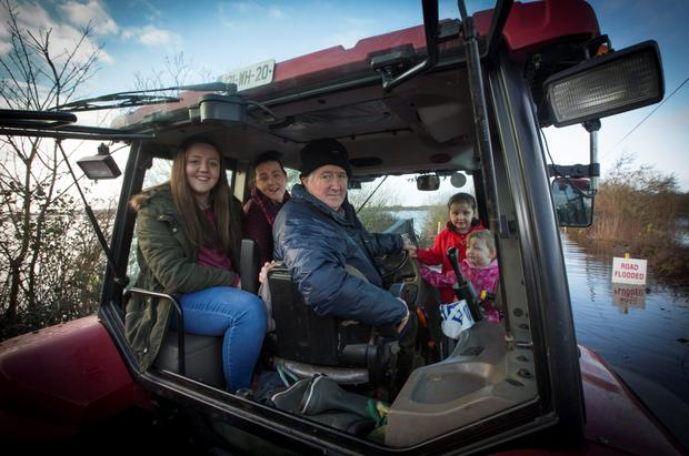 George Dooley with his daughter Carmel Boyce, second from left, and her children Louise (15) Eimer (six) and Maria (three), as he helps family and friends through the floods in his tractor in Athlone yesterday. Photo: Fergal Phillips.