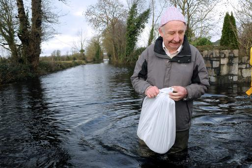 Resident John Killeen hitching a boat ride to get to the local shop in Springfield, Co Clare. Photo: Gareth Williams