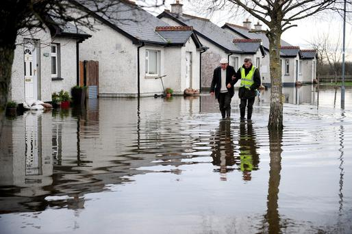 Noel Jones (81) is escorted from his flooded home in the Portavolla housing estate, Banagher, Co Offaly. Photo: APX