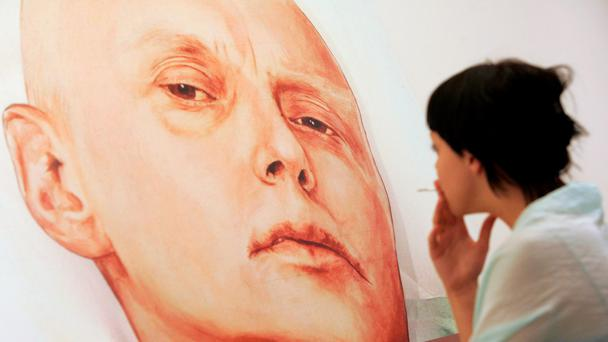 CROSSFIRE: A 2007 photo shows a woman looking at painting of former Russian spy Alexander Litvinenko in his hospital bed. Photo: Getty
