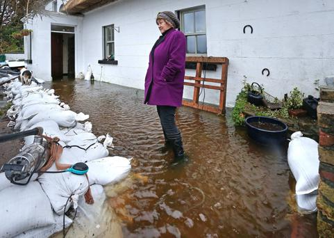 Bridie Willers outside her home at the height of the flooding. Photo: Andrew Downes