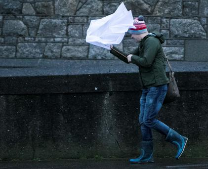 A commuter struggles with an umbrella in the wind. Photo: Kyran O'Brien