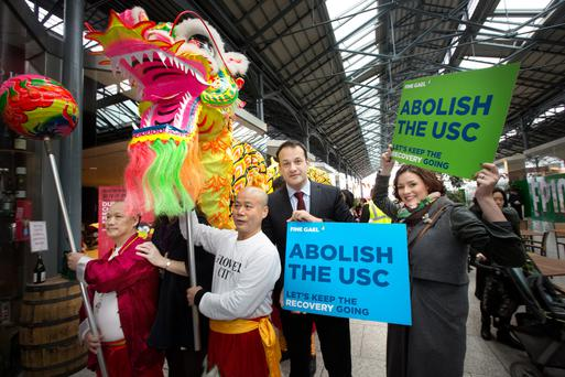 Health Minister Leo Varadkar and election candidate Kate O'Connell, Dublin South, meet the Flower City cantonese dragon group after Fine Gael's press conference on the party's plans to abolish the USC at CHQ Building in Dublin yesterday. Photo: Tony Gavin