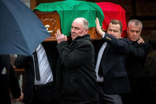 The coffin of Fr Peter Quinn, draped in the Mayo colours, leaves St Patrick's Church, Ballina, Co Mayo. Photo: James Connolly