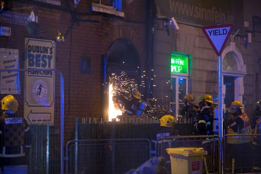 A firefighter cuts through a door beside the chip shop. Photo: Sam Boal