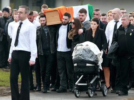 Kelly Smyth walks with her buggy as the remains of Vinnie Ryan are carried to the Church of the Holy Trinity in Donaghmede, Dublin