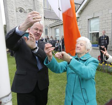Una Fletcher raises the Tricoulour with the help of Frank Colcannon, history co ordinator at St Josephs Boys National School in Terenure. Photo: Damien Eagers