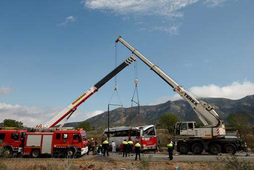 Cranes lift the wreckage of the coach that crashed near Barcelona. Photo: Reuters