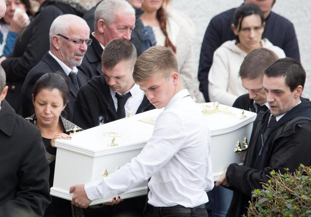 Louise James carries her son Evan's remains into their home. Photo: North West Newspix