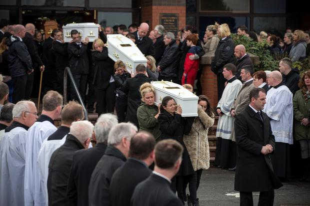 Louise James helps carry the first of the five coffins from the Holy Family Chapel, Ballymagroarty, Derry, after the funeral mass. Photo: Mark Condren