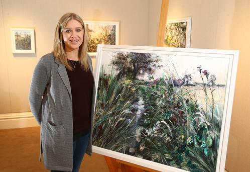 Emma Spence, sister of late Ulster rugby star Nevin (below) with one of the paintings from her new exhibition, 'Their Fields'