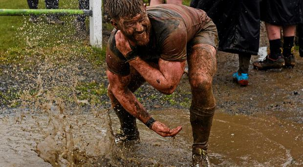 Liam Gaffney from Wicklow washes the mud off himself in a puddle at Oakpark in Carlow after the Bank of Ireland Provincial Towns Cup semi-final against Clondalkin Photo: Sportsfile / Paul Mohan