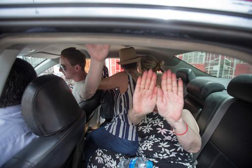 Family and friends try to prevent Michaella McCollum from being photographed in Lima, Peru, yesterday. Photo: Mark Condren