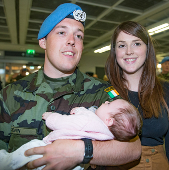 Private Stephen Cronin, from Cobh, with his five-week-old daughter Robyn and partner Jade White at Dublin Airport last night Photo: Arthur Carron