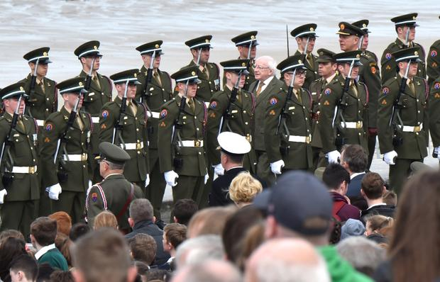 President Michael D Higgins walks between two lines of troops at the commemoration at Banna Strand yesterday. Photo: Domnick Walsh