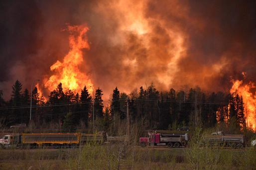 The wildfire rages along a highway near Fort McMurray, Alberta, Canada Photo: Reuters